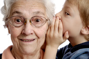 Child wispering in grandmothers ear